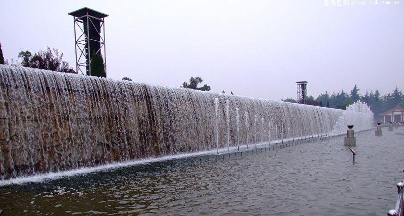 北广场音乐喷泉规模宏大,体现出古都王者风范。喷泉位于广场的中轴线上,南北最长约350米,东西最宽处110米,T字型结构,共分为百米瀑布水池、八级叠水池及前端音乐水池三个区域,既可分区独立表演,也可整体表演。喷泉样式多变,水柱形态各异,在灯光的映照下更显娇嫩、多姿。水柱腾空,四散而下,似莲花,状彩蝶,水珠相交,水雾蔓延,又好似千百海鸥振翅、南山茫茫云海。广场中心还有60米高喷水柱。水柱直飞冲天,气势壮观、磅礴。随风散落的颗颗水珠,在灯光的映射下迸发出晶莹的光洁,犹如剔透的珍珠漫天飞舞在广场上空,旋即幻化为肆